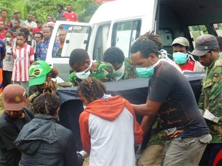 Jenaza korban di turunkan dari mobil jenaza untuk di makamkan